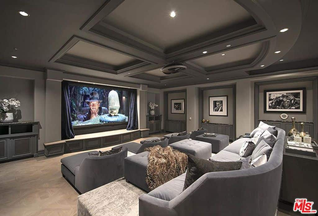 Gorgeous custom home theater with stadium seating and ceiling beams.