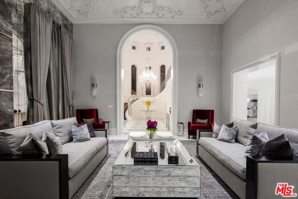 Stylish formal living room in mega mansion with two facing sofas adjacent to massive foyer.