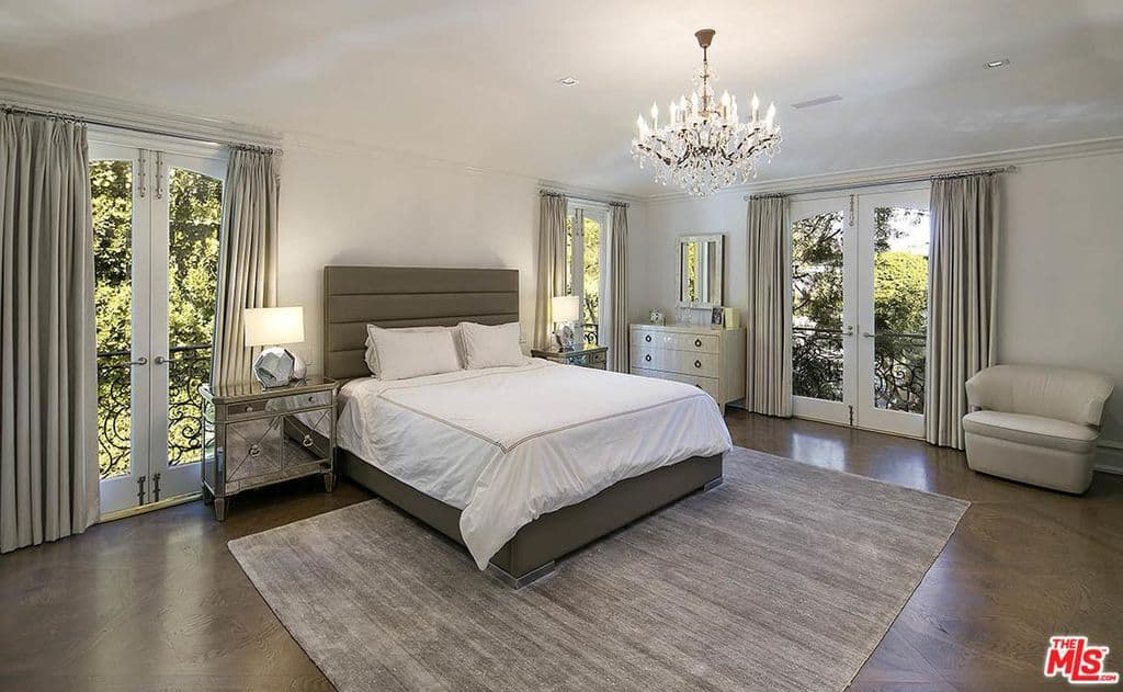 Glam guest bedroom surrounded with French doors that open to the ornate balcony. It is lighted by a fabulous chandelier and geometric table lamps that sit on mirrored nightstands.