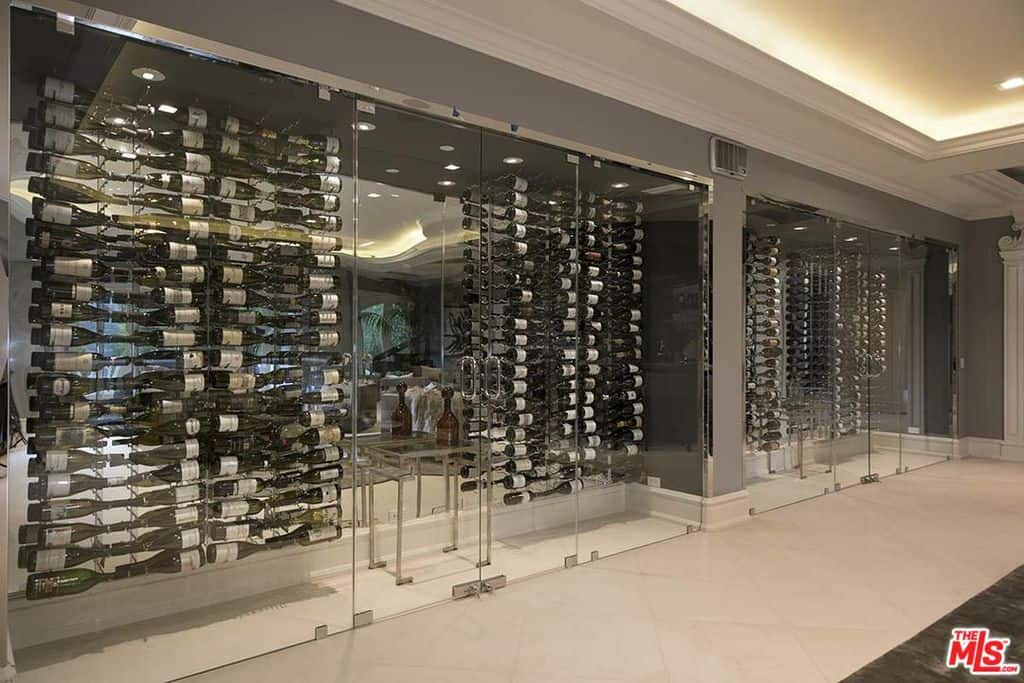 A lavish, modern wine cellar covered with glass enclosure displaying vertical wine racks mounted on the mirror glass walls.
