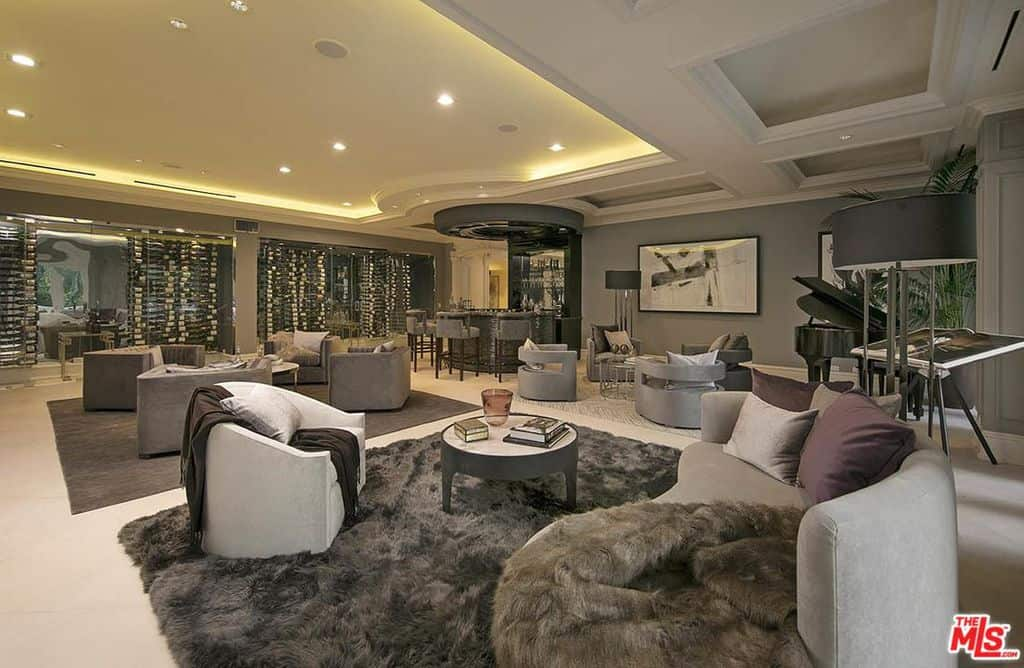 This great room features an elegant living room set and a classy bar, both under the stunning ceiling with beautiful ceiling lights.