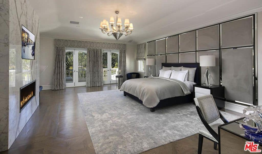 Huge primary bedroom with chandelier and fireplace.