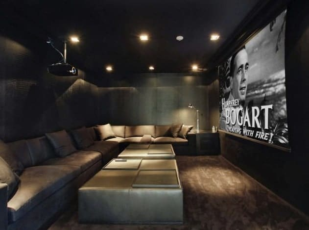 The home theater boasts a huge wide screen theater TV partnered by sectional sofa with a stylish carpet lighted by recessed ceiling lights.
