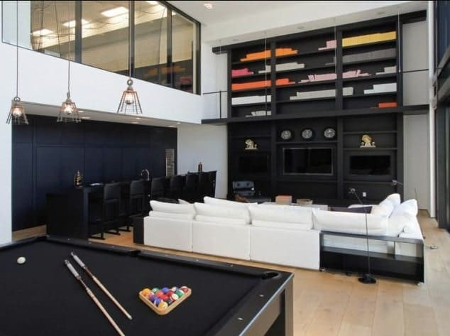 Large modern living room boasting white sofa set with black TV stand and shelves along with the black bar area matching the elegant black billiards pool set on the hardwood flooring.