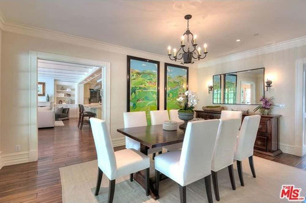 The rectangular dining table is lighted by a chandelier. White walls and hardwood flooring surrounds the room.