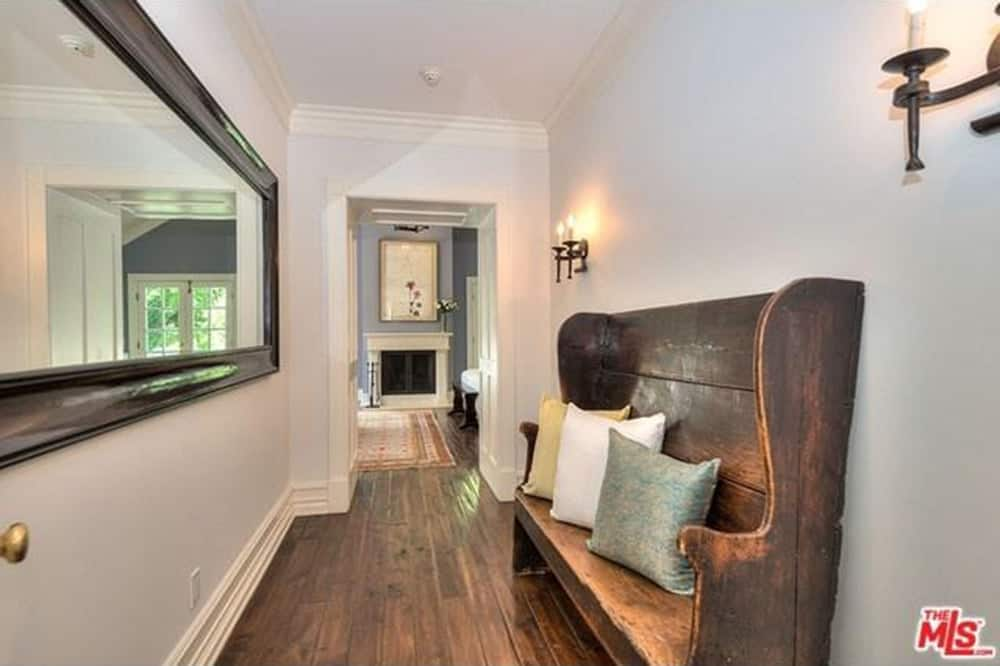 The hallway has a hardwood seating on a hardwood flooring lighted by wall lights.
