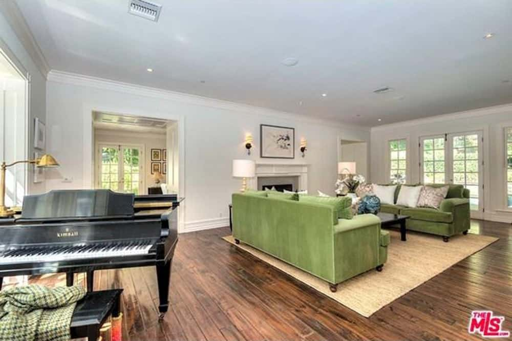 The formal living room surrounded by white walls and hardwood flooring boasts a grand piano and green sofa set with a rug.