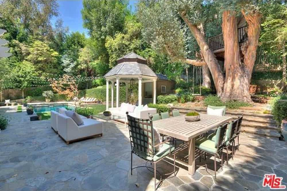This patio patio area offers a set of white furniture and a glass center table along with a 8-seat dining table set.