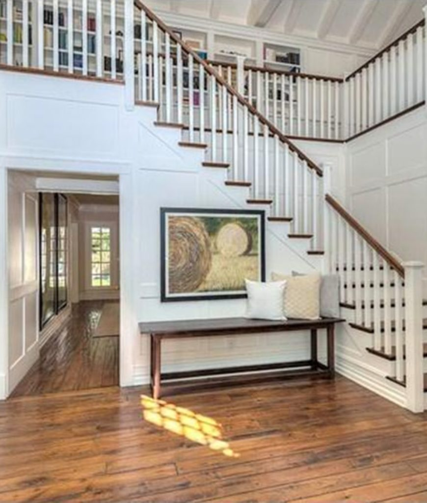 The 2-storey grand foyer features a hardwood flooring and white walls.