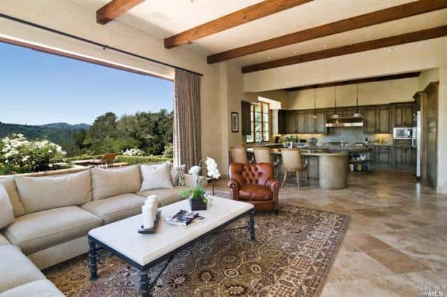 Great room boasts tiles flooring topped by a rug and beams ceiling. Open way to terrace provide amazing view of the landscape and Phoenix lake.