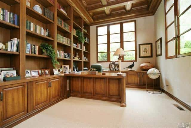 The mansion also has a home office featuring coffered ceiling and huge bookshelf on a carpet flooring.