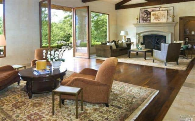 The living room featuring a mediterranean style boasts a hardwood flooring topped by rug matched by beams ceiling.