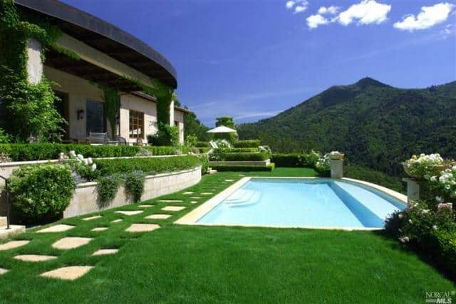 A spectacular swimming pool surrounded by healthy green lawn mirrors the bright sky.