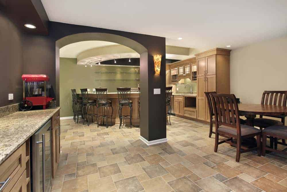 Large open basement with a bar area and a dining nook set on the tiles flooring.