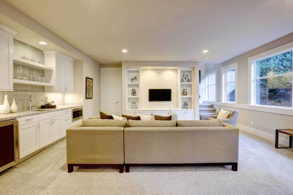 Beautiful basement family room totally refinished with recessed lighting, carpeting and large sofa.