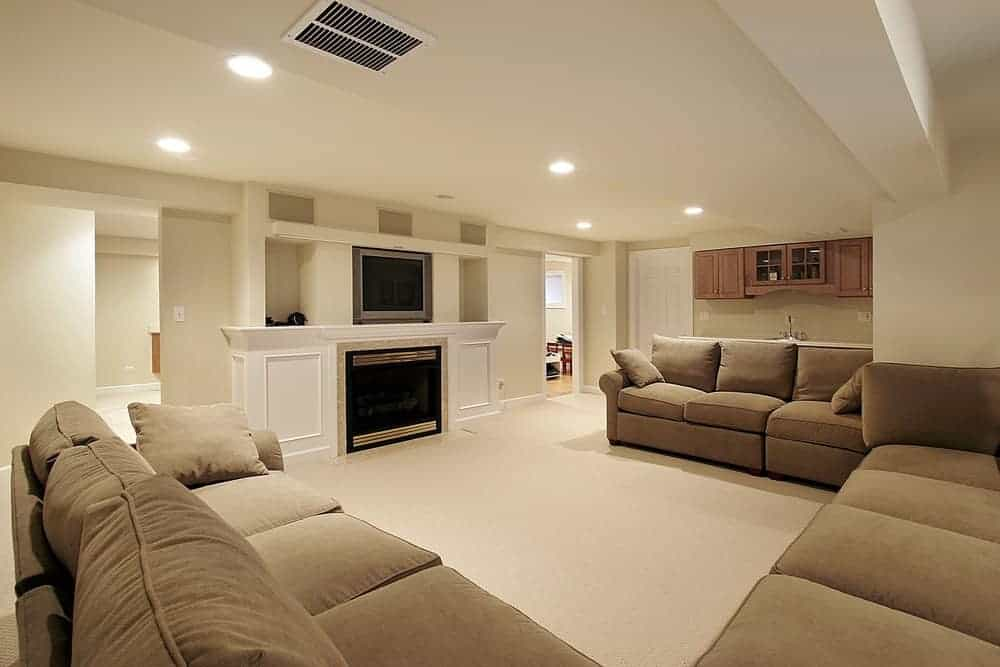 Large basement family room with TV and fireplace along with cozy sofa set and carpet flooring.
