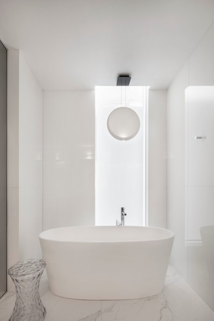 Pure white master bathroom with smooth marble flooring and a large freestanding tub along with a walk-in shower.