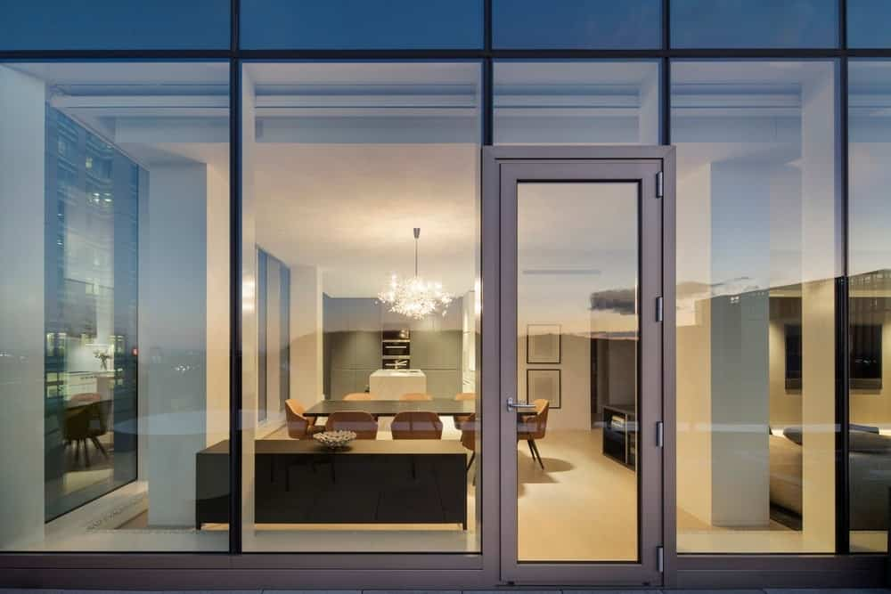 Modern home with glass windows and doorway leading to terrace. Photo Credit: Adrien Williams