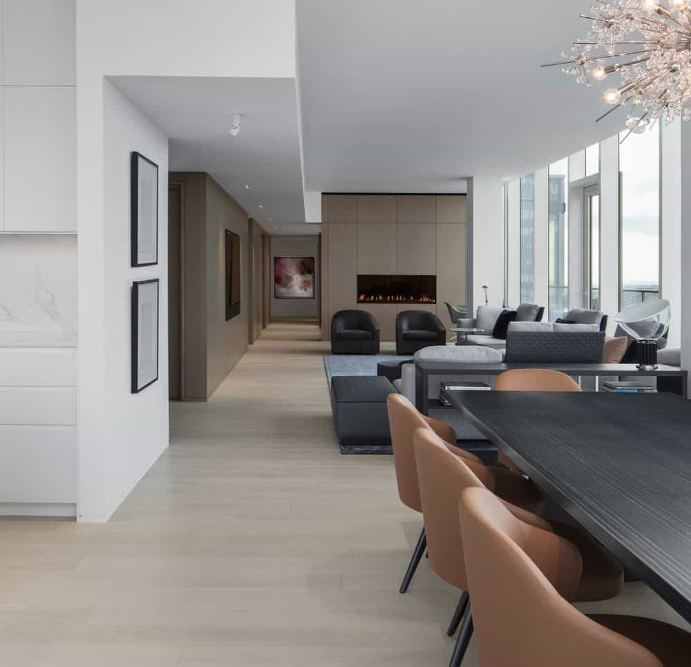 Living space and dining area on a hardwood flooring with white ceiling and glass windows. Photo Credit: Adrien Williams