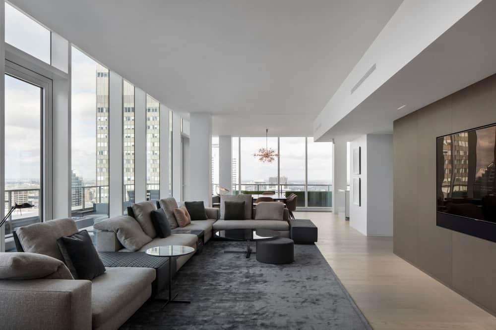 Modern living room stylish sofa set and rug along with hardwood flooring and glass windows. Photo Credit: Adrien Williams