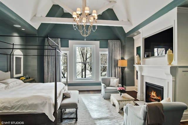 Gorgeous primary bedroom boasts a metal canopy bed and a lovely chandelier that hung from the vaulted ceiling framed with white wood beams.