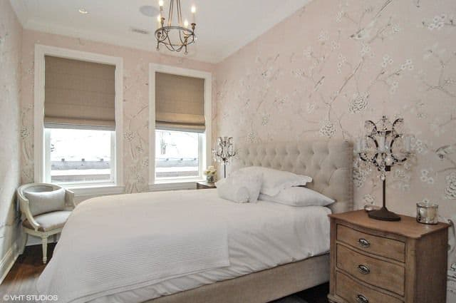 The bedroom features a pink with white accent lighted by a candle light chandelier.