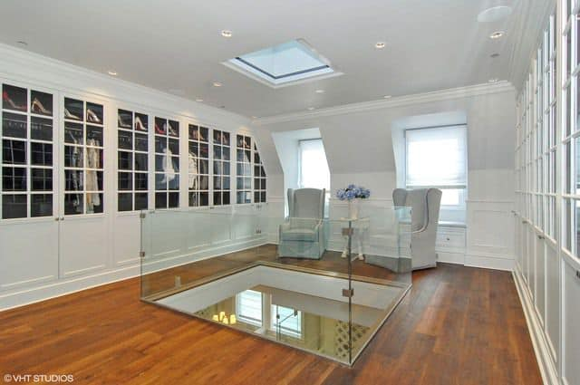 The home also has a huge walk-in closet with two chairs on a hardwood flooring.
