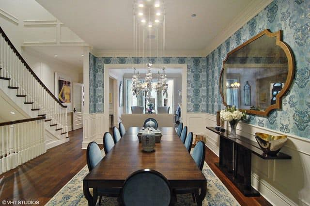 Stylish dining area features a fabulous chandelier and a huge mirror that hung above the dark wood table topped with a flower vase and decorative bowl. It has a wooden dining set that sits on a lovely blue rug complementing with the wallpaper.