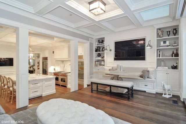 A living space next to the kitchen area. It features a dining nook and a couple of bookshelves. The white coffered ceiling perfectly fits with the room's style.