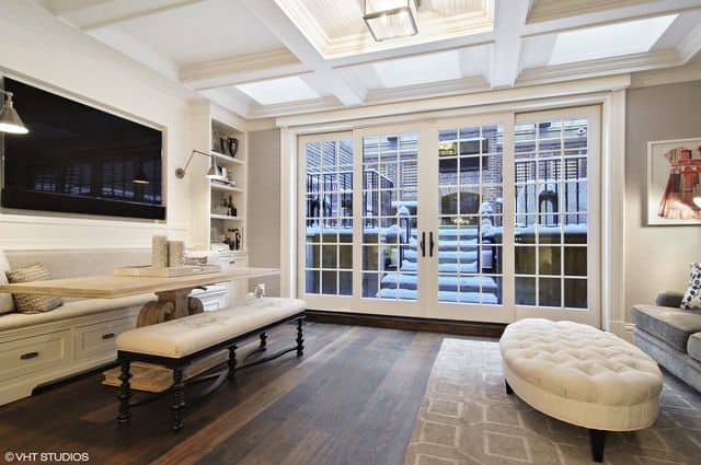 Another living space offers entertainment from the TV on wall. Coffered ceiling adds style to the room while french door leads to outdoor area.