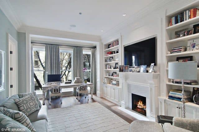 The home boasts a home office featuring a couple of built-in bookshelf with a wide TV in the middle. Just below of the TV is the fireplace to keep the temperature warm.