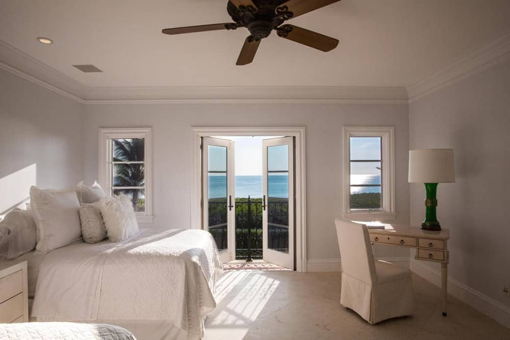 The pure white bedroom features a french door leading to a private balcony.