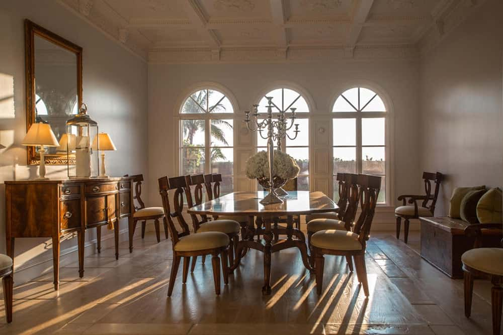 The dining room surrounded by white walls and coffered ceiling features an elegant dining set.
