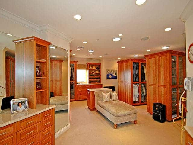 Large bedroom closet boasting a set of walnut finished cabinetry along with a center island. Scattered recessed lights brighten the space.