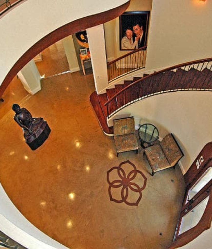 The foyer features a long spiral staircase lighted by pendant lights.