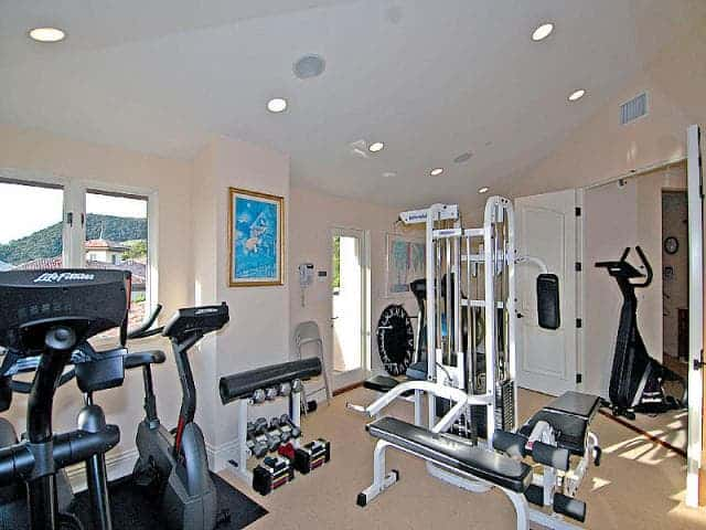 The Gym Features An Almost Complete Set Of Machines. The Room Is Lighted By  Multiple Recessed Ceiling Lights.