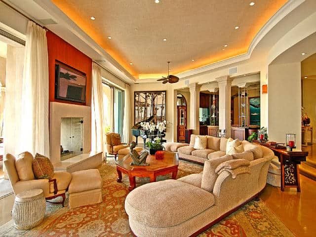 An elegant formal living room with a large fireplace and a gorgeous large rug. The tray ceiling along with its lighting looks absolutely stunning.