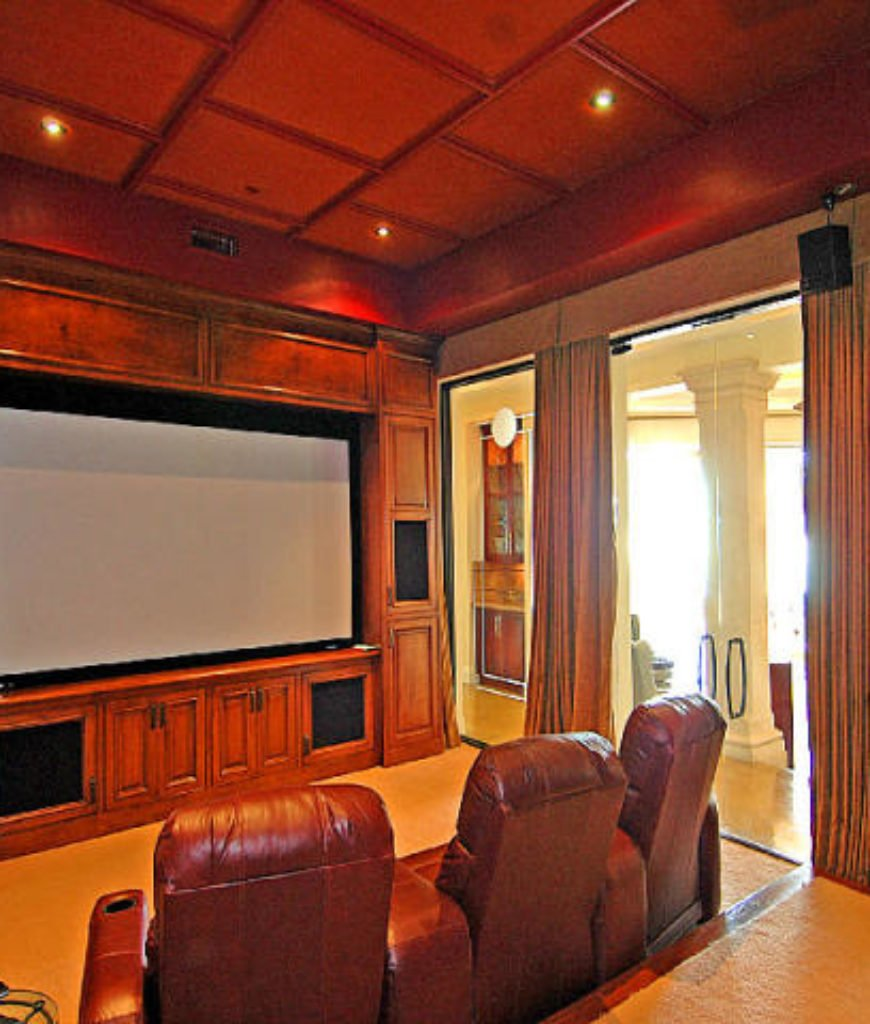 The home theater features a glass door and walls with elegant window curtains.