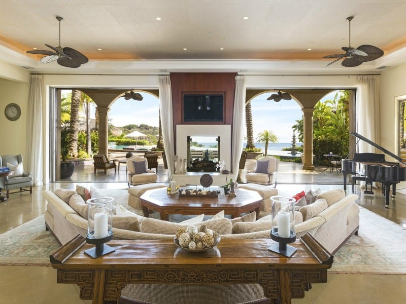 This mansion offers a formal living space near the stunning outdoor area. There's a piano on the side. The sofa set looks perfect together with the walls and floors.