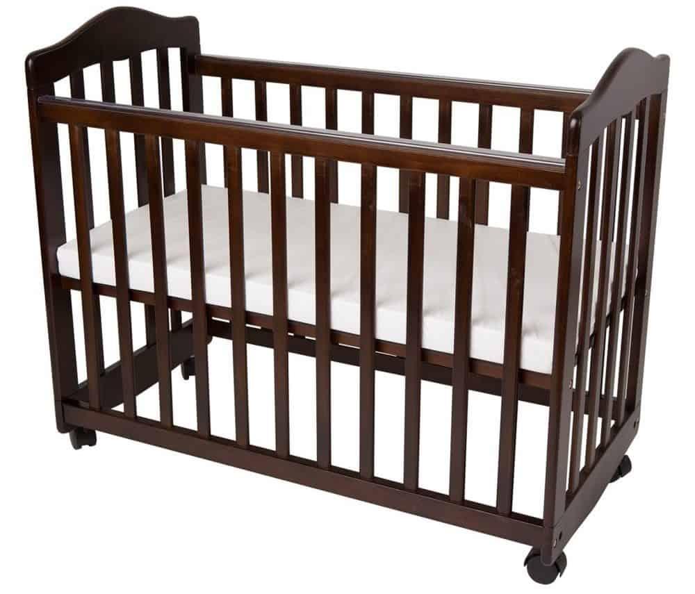 Dark-brown baby crib with a white mattress.