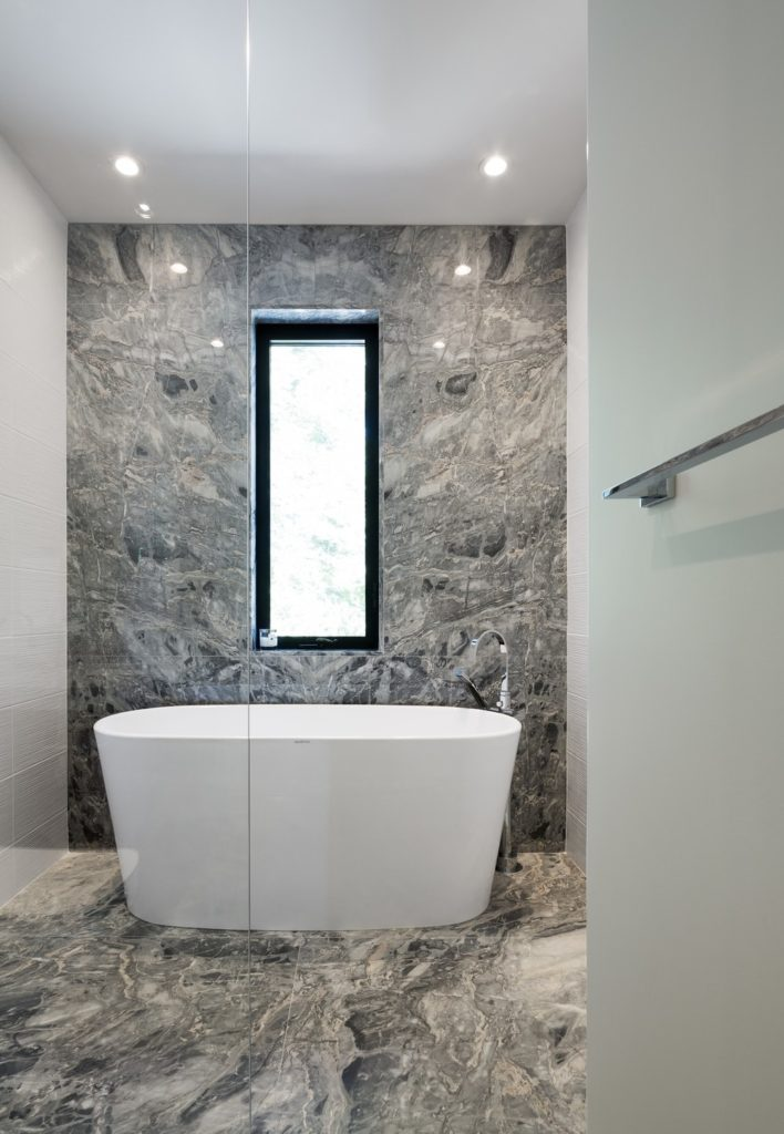 Modern master bathroom with stylish flooring and walls along with a large freestanding tub.