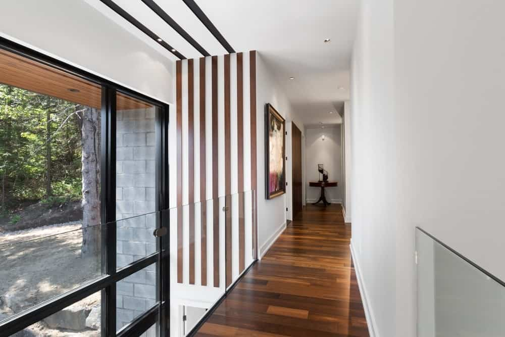Hallway featuring laminated flooring with white walls and recessed ceiling lights. Photo credit: Steve Montpetit