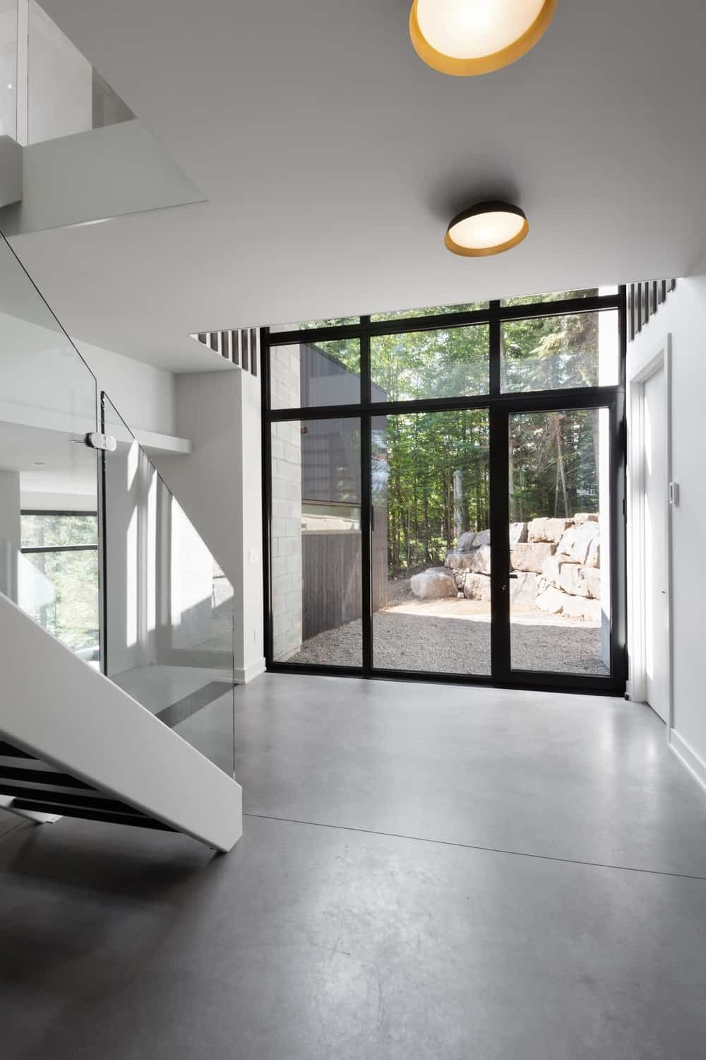 Entryway of the house featuring glass door and white walls along with a staircase. Photo credit: Steve Montpetit