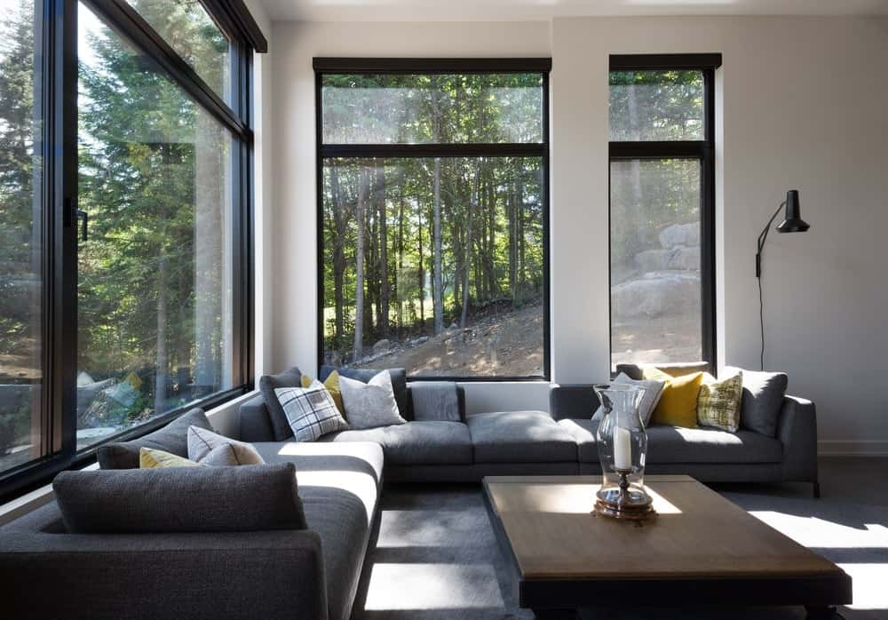 Living room with modern sofa set and rug along with white walls and glass windows. Photo credit: Steve Montpetit