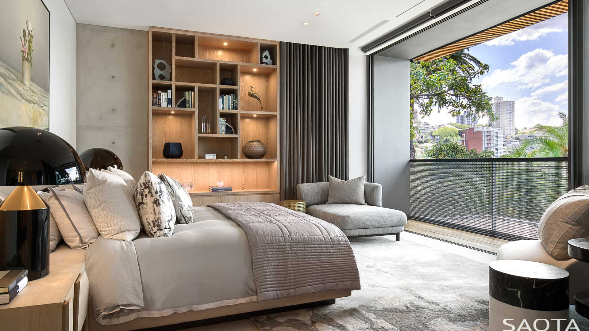 Airy primary bedroom features built-in wooden shelves and black railings. It includes a gray bed matching the lounge chair that's lighted with black table lamps.