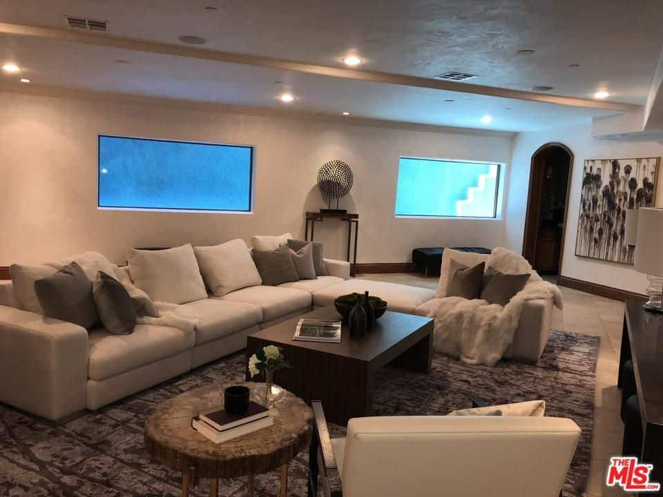 Contemporary family room in a mediterranean style room also exists in Eva Longoria's house. The room is lighted by recessed lights while sofa set perfectly fits with the rug.