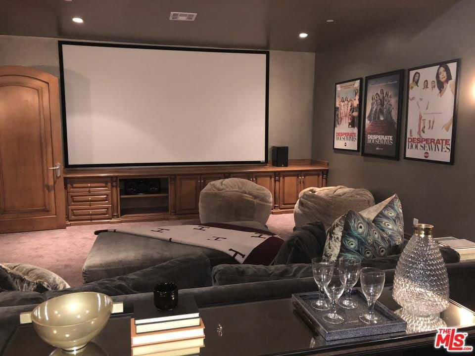 The House Also Boasts A Home Theater With A Huge TV Lighted By Recessed  Lights. Carpet Flooring Matches Well With The Sectional Sofa.