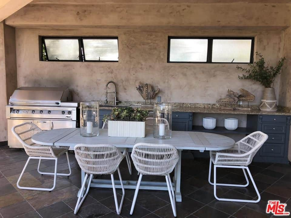 The house includes an outdoor kitchen with a 6-seater oval dining table and stainless steel appliance.