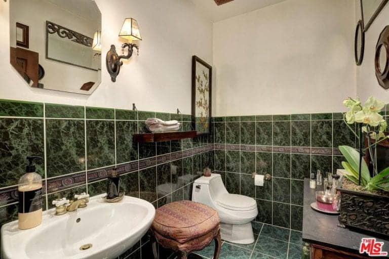The bathroom feature green tiles and wall lighting. The room also has a table with cabinet along with a single seat.