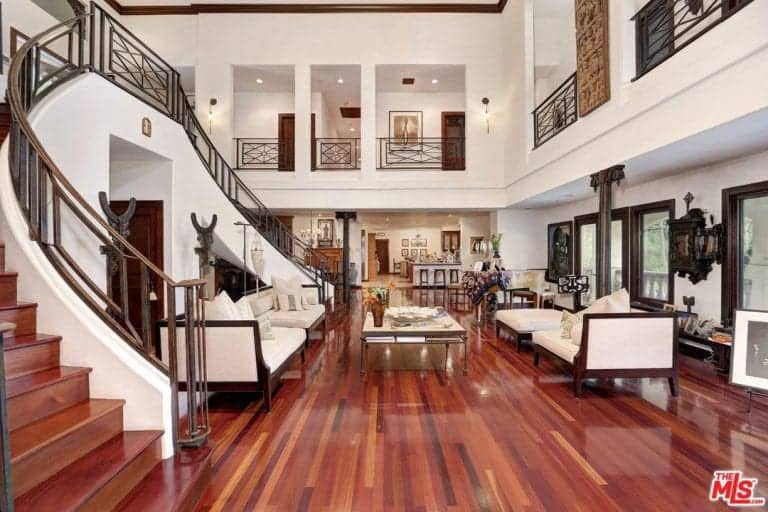 Large Mediterranean living room with reddish hardwood flooring and white walls matching the white seats. The high ceiling and beautiful staircase make this living room look so stunning.